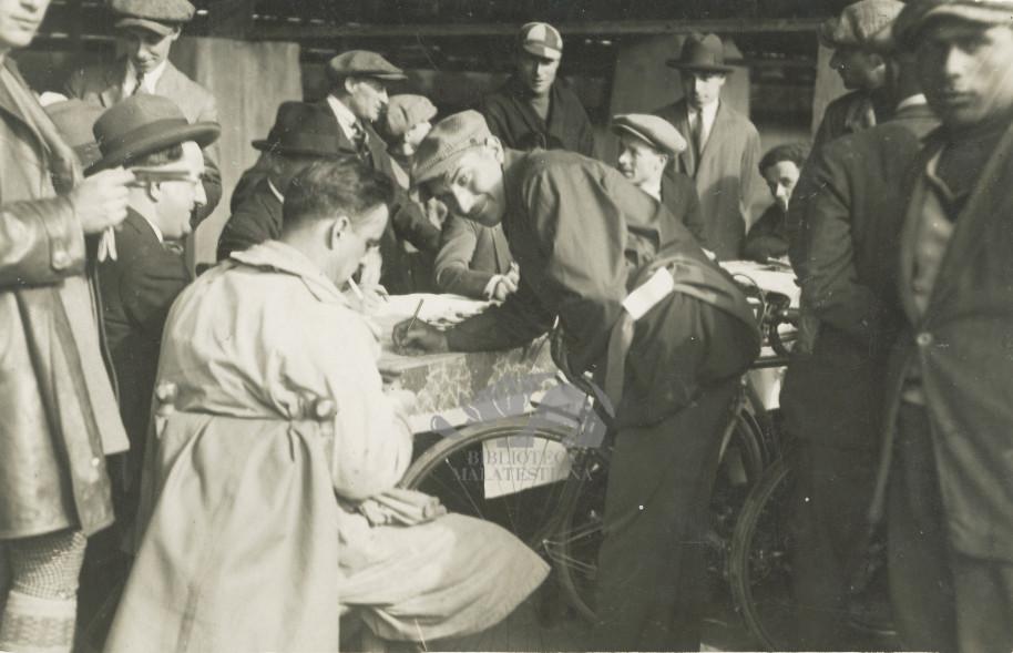 Giro d'Italia 1913: punzonatura: Ambrosini visto di spalle al tavolo di registrazione. Foto L'Ambrosiano